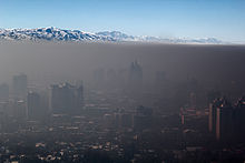 Dense, smokey air lays over a cityscape like a blanket. In the distance, a mountain range and clear blue sky can be seen.