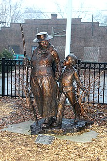 A metal statue of Tubman holding the hand of a small child