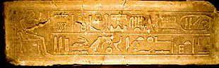 Groot blok steen bedekt met een zittende man tegenover een grote hiëroglifische tekst aan de linkerkant