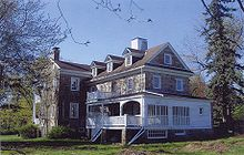 A large stone house with many dormers, windows, and a white porch, surrounded by trees