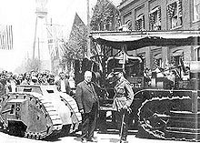 A military man in full dress uniform salutes a suited business man who is doffing his bowler hat in return. Behind the two men is a Holt tractor, which towers above them, and a diminutive one-man tank, which is below chest height. Behind the vehicles, a crowd looks on.