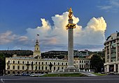 a picture a city square with a large pillar with a golden statue on top in the foreground and a large building with a steeple in the background