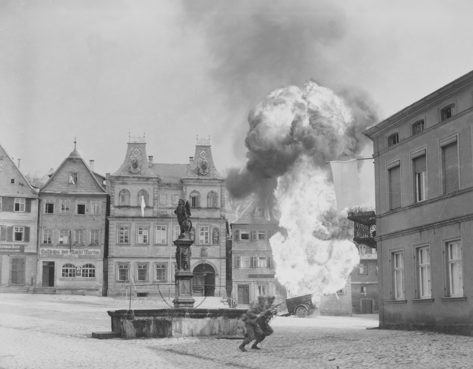 Two anti-tank Infantrymen of the 101st Infantry Regiment, dash past a blazing German gasoline trailer in square of... - NARA - 531289 Croped, stants deleted
