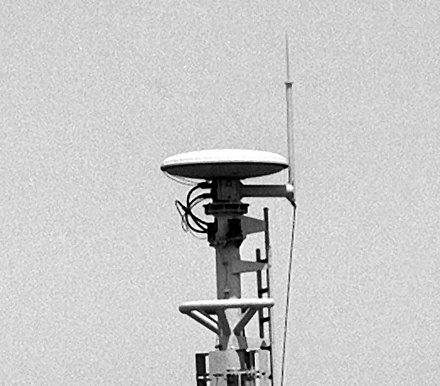 A shipboard TACAN antenna on USS Raleigh (LPD-1) with a lightning rod extending above it. - Tactical air navigation system