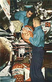 U.S. Navy enlisted man lifting a bag of potatoes surrounded with other bag and cases of food in a submarine torpedo room.