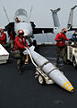US Navy 030321-N-9593M-063 Aviation Ordnancemen move a Joint Direct Attack Munition (JDAM) across the flight deck of USS Abraham Lincoln (CVN 72).jpg