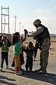 US Navy 050210-M-5585B-014 U.S. Navy Hospital Corpsman 2nd Class Robert Sanders plays patty cake with local Iraqi children in the village of Al Madinah, Iraq.jpg