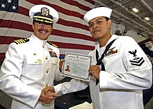 Two men in white Navy uniforms, shaking hands, holding up a certificate, in front of a large American red&white&blue flag.