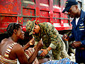 US Navy 100204-N-1033Q-117 Hospital Corpsman 3rd Class Philip Davila xamines a Haitian woman's leg as Chief Warrant Officer Wilfrid Bossous translates.jpg
