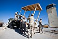 US Navy 101115-N-6383T-473 Seabees assigned to Naval Mobile Construction Battalion (NMCB) 18 and U.S. Air Force personnel unload an equipment shelt.jpg