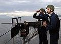 US Navy 110128-N-5620H-082 Gunner's Mate 1st Class Curtis Luttrell and Gunner's Mate 2nd Class Steven Berrey keep watch as USS Frank Cable (AS 40).jpg