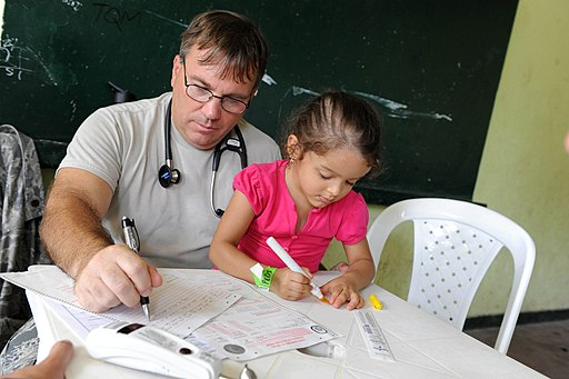 US Navy 110609-F-ET173-228 Maj. Gary Ruesch completes medical forms as his patient draws a picture at the Escuela Max Seidel medical site in Tumaco