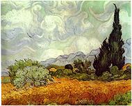 An open field of yellow wheat, under swirling and bright white clouds in an afternoon sky. A large cypress tree to the extreme right painted in shades of dark greens with swirling and impastoed brushstrokes. There are several smaller trees to the left and around the cypress tree are more small trees and several haystacks. There are blue-gray hills on the horizon in the background.