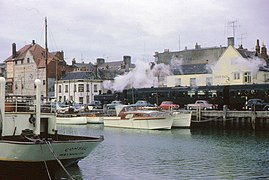 A green pannier tank locomotive is pulling green passenger coaches past a row of parked cars. In the foreground is a harbour with moored pleasure craft. Behind the train is a row of buildings.