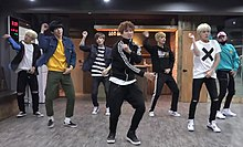 Seven young men performing synchronised dance moves, wearing casual clothing. Some of them have dyed hair.