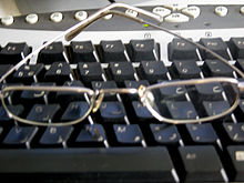 A pair of glasses sitting on a computer keyboard.