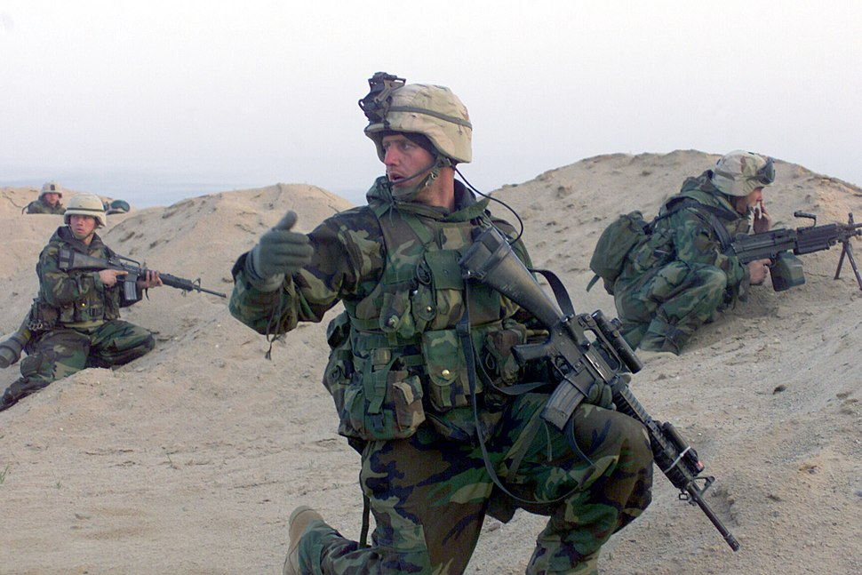 030323-M-3692W-014 Sgt. Jeff Seabaugh, a squad leader with the 15th Marine Expeditionary Unit (Special Operations Capable) (15th MEU (SOC)), moves his Marines to their objective during a mission in the Iraq War