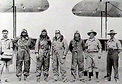 Seven men, four in flying suits, standing in front of the wings of two biplanes