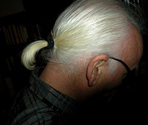 Ponytail - Man's white-haired ponytail on a black background.