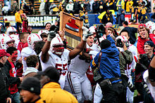 A group of American football players, surrounded by photographers, lift a plaque upon which is an ax head and an inscription.