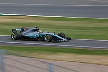 Photo of Lewis Hamilton driving a silver Mercedes on a racetrack