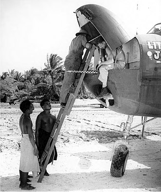 Hawkins Field (Tarawa) - Armorers place a .50-caliber aircraft John Browning machine gun M2A1 in the nose of a 41st Bombardment Group North American B-25 Mitchell at the airfield on Hawkins Field as interested natives look on