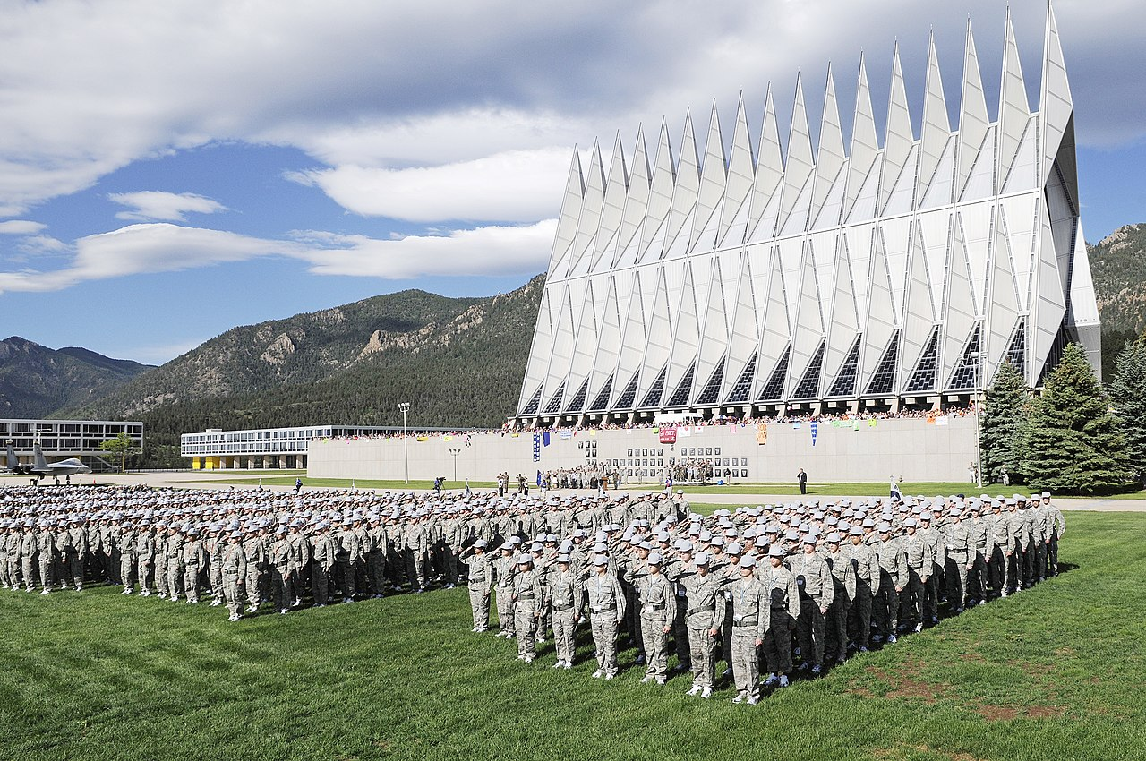 A very large group of mostly male-presenting people in combat fatigues and hardened caps stand at attention and salute in a grassy field before high modernist buildings. The Rocky Mountains ring the campus. The sky is blue and light direct.
