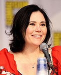 A woman with black hair, tied back, smiling, and sitting behind a microphone.