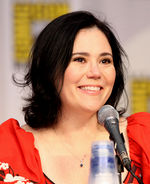 A caucasian woman with black hair tied back, smiling into a microphone, with a vague symbol behind her.