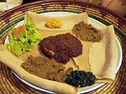 Typical Ethiopian cuisine: Injera (pancake-like bread) and several kinds of wat (stew).