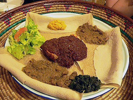 This meal, consisting of injera and several kinds of wat (stew), is typical of Ethiopian and Eritrean cuisine. Alicha 1.jpg