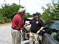 Anderson County Sheriff John Skipper presents a coin and thanks to U.S. Army Staff Sgt. Bryan Davis, a provost marshal member, in Starr, S.C., Aug. 10, 2013, for assisting with security in response to the rescue 130810-Z-LJ054-005.jpg