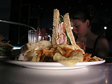 A club sandwich and potato chips on a plate at the Sci-Fi Dine-In