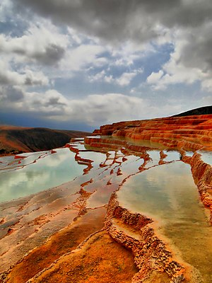 Travertine - Badab-e Surt's stepped travertine terrace formations. The red color of travertine terraces is due to iron carbonate.