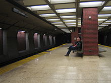A near-empty station platform of an underground train station, with a man sitting on a bench