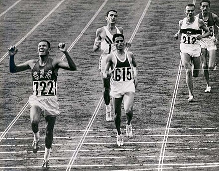 Billy Mills crosses the finish line at the end of the 10,000-meter race at the 1964 Tokyo Olympics. BillyMills Crossing Finish Line 1964Olympics.jpg