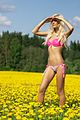 Blond woman in a pink underwear on a field with yellow flowers 01.jpg