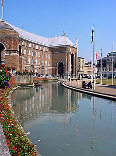 A large brick building, built in a shallow curve, with a central porch. In front of that a pool and a water fountain.