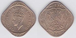 Zwei viereckige Münzen aus dunklem Metall nebeneinander, auf einer Ecke stehend. Die linke Münze zeigt einen Kopf mit Krone der nach links schaut. Auf der rechten Münze steht INDIA, in der Mitte die große Zahl 1/2 und darum herum sind Verzierungen.