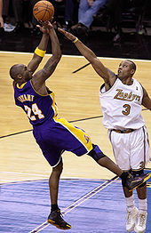 "Kobe Bryant making a ""fade"" basketball shot attempt over defender Caron Butler"