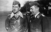 Black-and-white photograph showing half-length view of two uniformed men outdoors, standing next to each other.