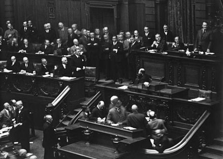 The Reichstag, 12 September 1932: Chancellor Franz von Papen (standing left) who wants to declare the dismission, above at the right the Reichstag president Hermann Goring (NSDAP) who looks the other way. Bundesarchiv N 1310 Bild-048, Berlin, Reichstagssitzung.jpg