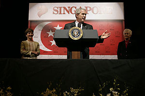 Flag of Singapore - United States President George W. Bush addressing U.S. Embassy staff in Singapore on 16 November 2006. The national flag behind him is defaced with the Lion Symbol numerous times.