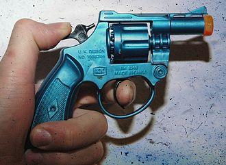 Toy gun - An orange-tipped cap gun with its hammer drawn back