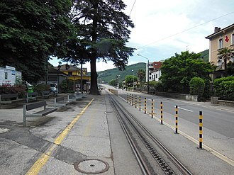 Capolago - Looking south along Capolago's main street, with the railway station (in yellow) and the track of Monte Generoso railway