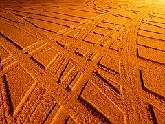 Car tire tracks in snow under sodium light.jpg