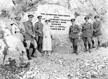 "Five soldiers in Sam Browne belts, riding boots and peaked caps, and one woman in light coloured dress and matching hat in front of a stone inscription that reads: ""The British XXI Corps with Le Detachment Français de Palestine et Syrie occupied Beirut and Tripoli October 1918 AD."""