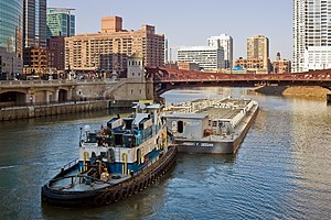 A tugboat pushing a barge westward along the m...