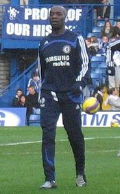A dark-skinned man wearing a sequential black jogging suit with blue lining.