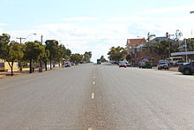 Photo of wide single carriageway road in a town